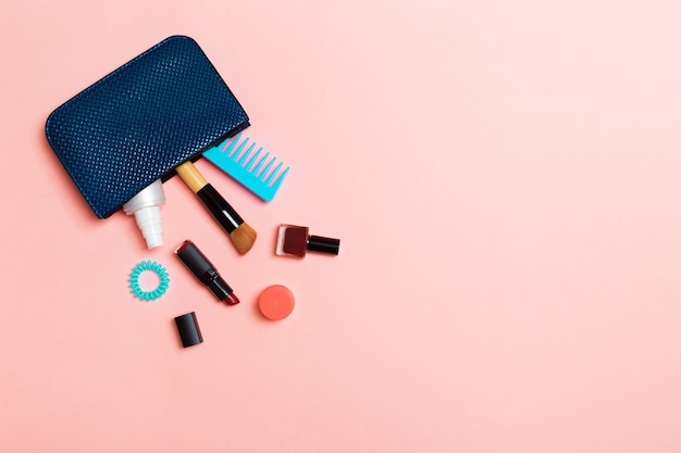 Make up products spilling out of cosmetics bag Premium Photo