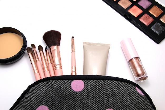Make up set cosmetics bag of decorative, makeup tools on white background. Premium Photo