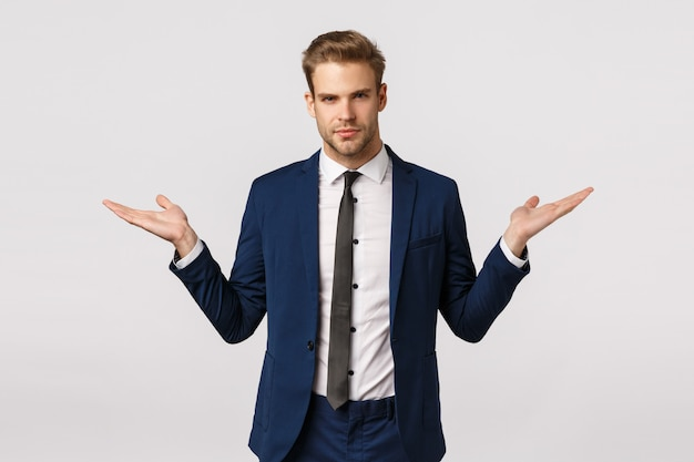 Make your choice. serious-looking assertive and stylish young blond businessman in classic suit, propose two variants gain money, become rich, spread hands sideways, hold product, white background Premium Photo