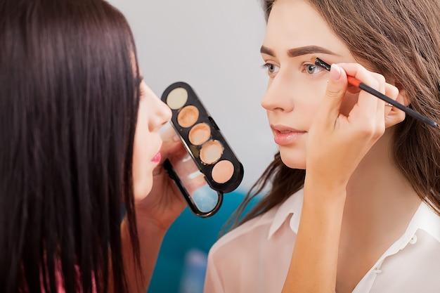 Makeup artist applies eye shadow. beautiful woman face. perfect makeup Premium Photo