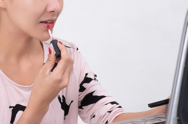 メイクアップアーティストは赤い口紅を塗ります。若い美容アジアモデルの女の子の唇を描く。白い背景で隔離のプロセスでメイクアップ Premium写真