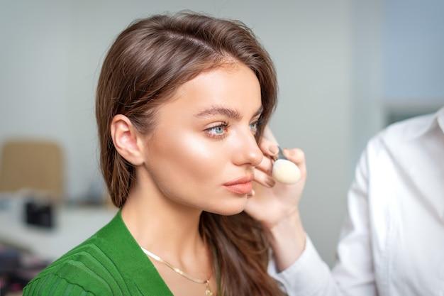 ビューティーサロンでブラシツールを使用して若い女性の顔に化粧品の色調ファンデーションを適用するメイクアップアーティスト Premium写真