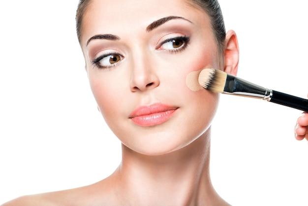여자 얼굴에 리퀴드 톤 파운데이션을 적용하는 메이크업 아티스트 무료 사진