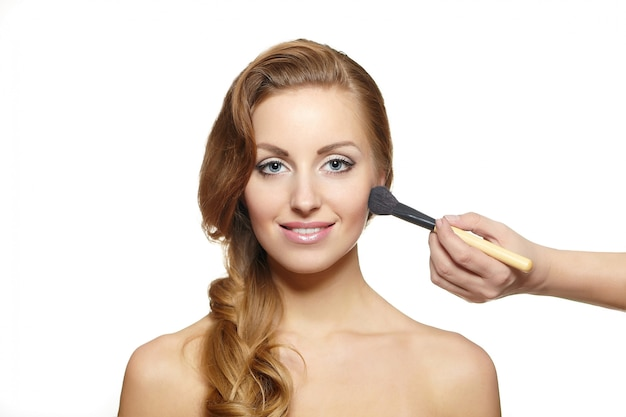 Makeup artist applying makeup to attractive blond woman Free Photo