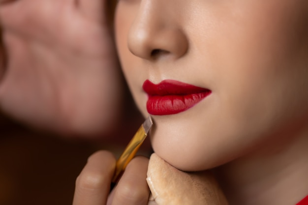 Makeup artist applying red lipstick on beautiful model mouth by using lip brush Premium Photo