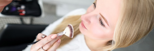Визажист держит косметическую кисточку у лица модели Premium Фотографии