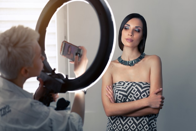 Makeup artist photographs on a mobile phone the result of his work Premium Photo