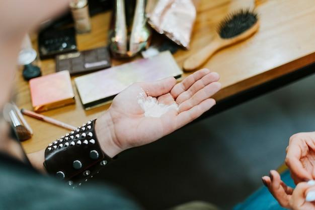 Makeup artist with translucent powder in his palm Premium Photo