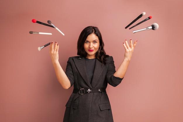 笑顔のメイクアップアーティストの女性とブラシやツールを投げる Premium写真
