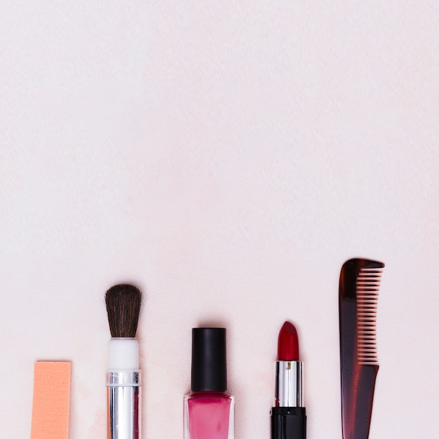 Makeup brush; nail varnish bottle; lipstick and comb on white textured backdrop Free Photo