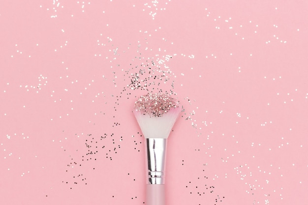 Makeup brush and shiny sparkles on pastel pink. festive magic makeup concept. Premium Photo