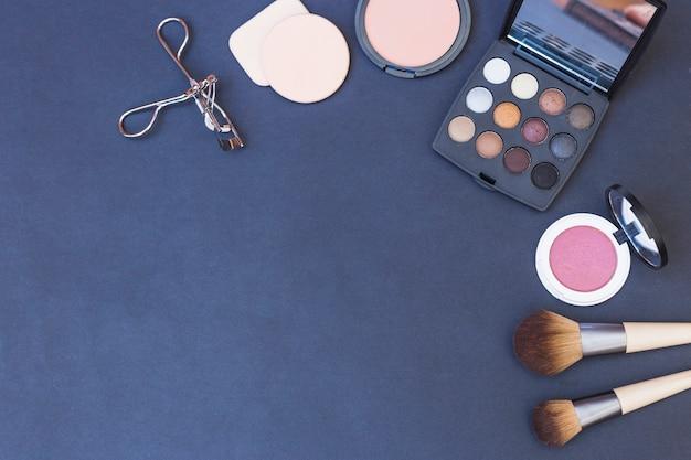 Makeup brush; sponge; blusher; eyeshadow palette and eyelash curler on blue background Free Photo