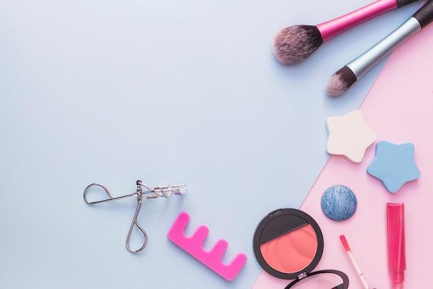 Makeup brush; star sponge; pink blusher; eyelash curler and lipstick on dual backdrop Free Photo