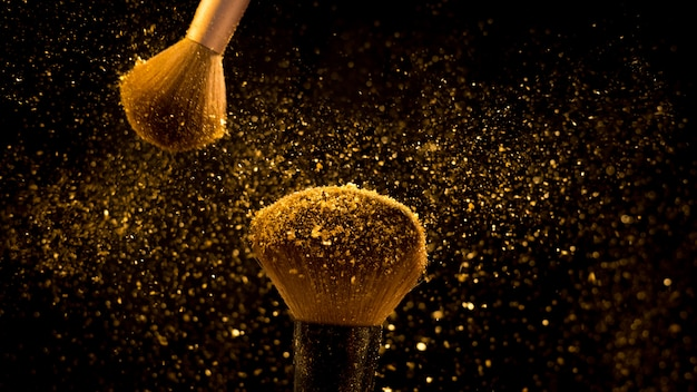 Makeup brush with golden cosmetic powder spreading on black background Premium Photo