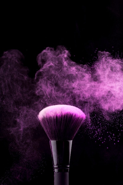Makeup brush with neon fuchsia powder mist Free Photo