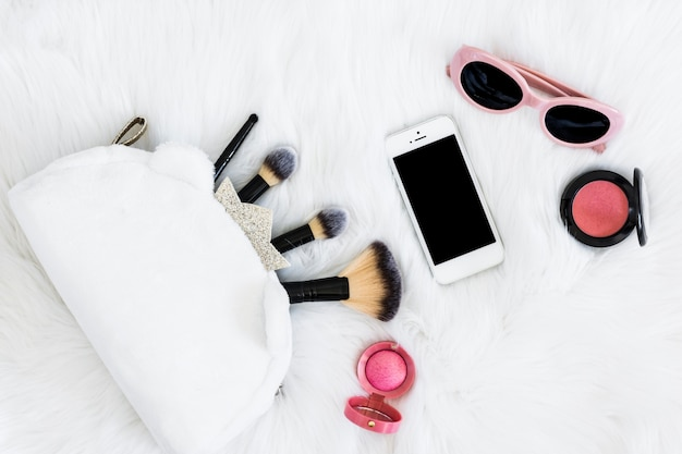 Makeup brushes in bag; mobile phone; sunglasses and pink compact face powder on white fur Free Photo