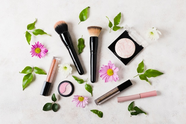 Makeup brushes and cosmetics with daises Free Photo