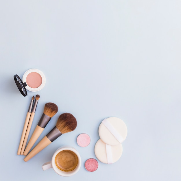 Makeup brushes; eye shadow; blusher and sponge with coffee cup on blue background Free Photo