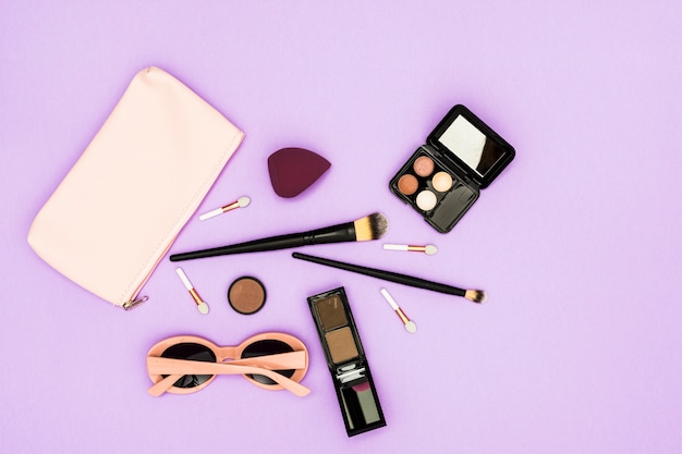 Makeup brushes; eyeshadow palette and sunglasses on purple backdrop Free Photo