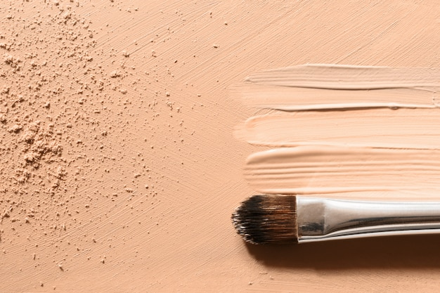 Makeup foundation, beige concealer smudges, face powder and cosmetic makeup brush Premium Photo