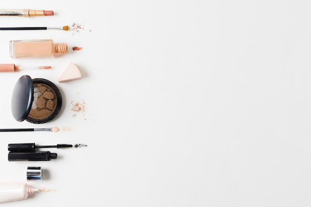 Makeup products arranged on gray background Free Photo