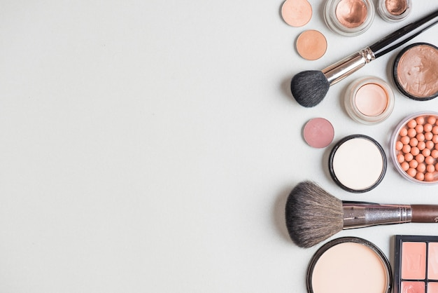 Makeup products and brushes on white backdrop Free Photo