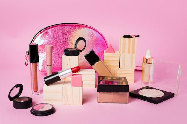 Makeup products and glossy cosmetic bag on pink background Free Photo