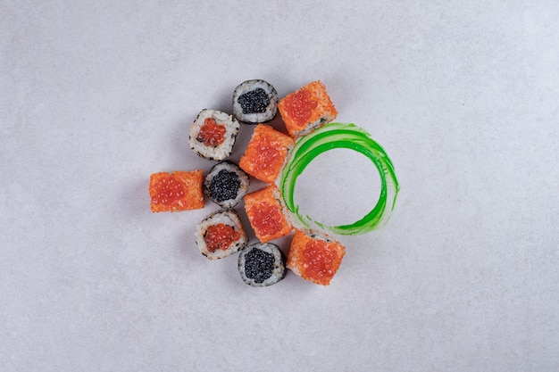 Maki, alaska e california sushi rotoli su sfondo bianco con anello di plastica verde. Foto Gratuite
