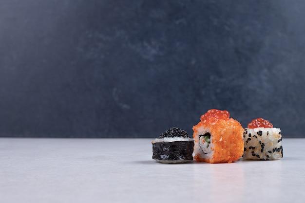 Maki, alaska e california sushi rotoli sul tavolo bianco. Foto Gratuite