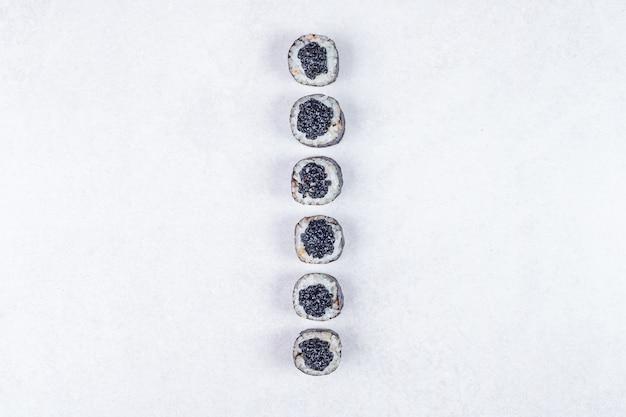 Rotoli di maki decorati con caviale nero su sfondo bianco. Foto Gratuite