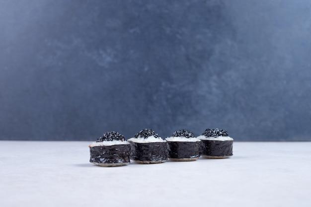 Rotoli di maki decorati con caviale nero sul tavolo bianco. Foto Gratuite
