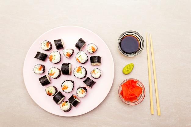 Маки роллы с имбирем, васаби и соевым соусом на розовой тарелке Premium Фотографии