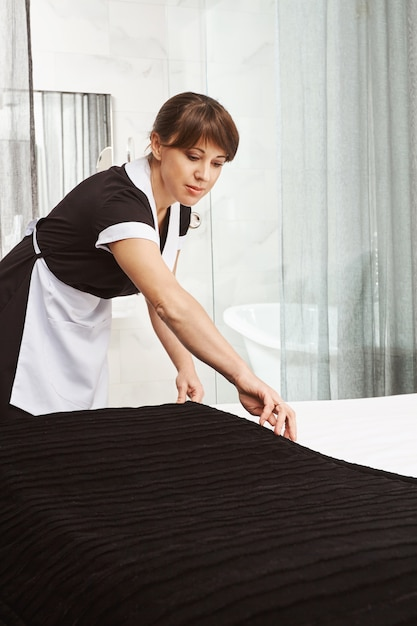 Making bed is like art. indoor shot of maid in uniform, putting blanket on bed while cleaning hotel apartment or house of owners, trying to wipe dust from all surface and offer best service Free Photo