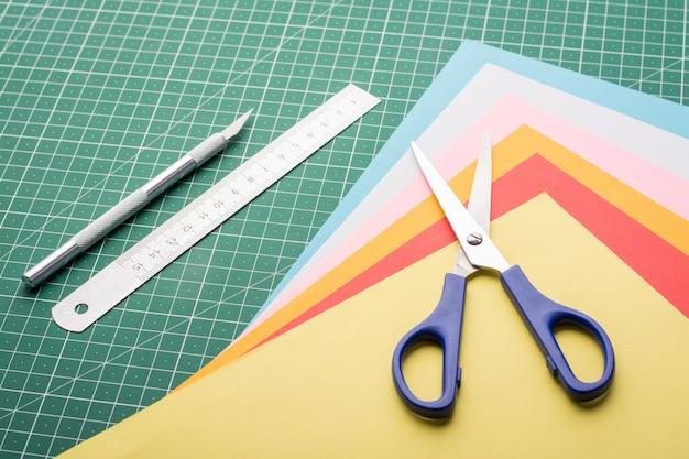 Изготовление разных моделей из бумаги. работа с бумагами. ножницы, скальпель, стопка бумаг и линейка на коврике Premium Фотографии