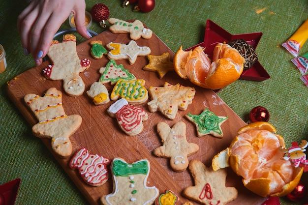 ジンジャーブレッドマン、クッキー生地を作る。家でのごちそう、家族の夕食のコンセプト。新年の伝統のコンセプトと調理プロセス。木製の緑のテーブルの上のクッキー。 Premium写真