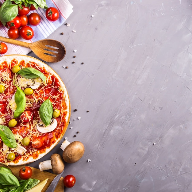 Making homemade pizza from dough with mushrooms, tomatoes and cheese Premium Photo
