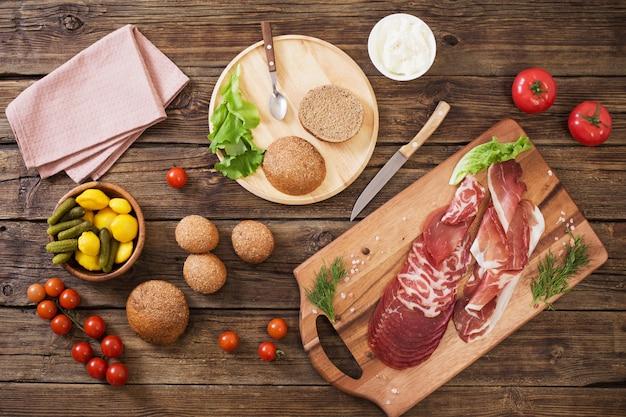 Изготовление бутербродов с мясом и колбасой на деревянный стол Premium Фотографии
