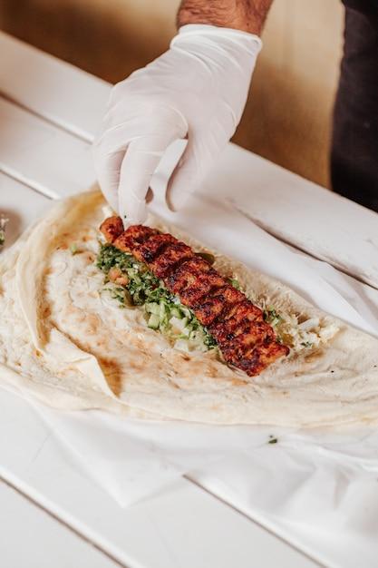 Making shawarma with kebab meat and arabic bread. Premium Photo