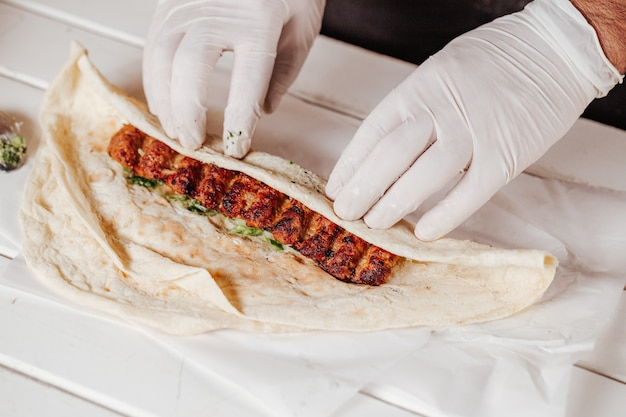 Making shawarma with kebab meat and arabic bread. Premium Photo