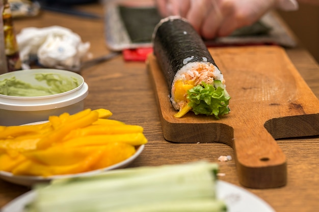 Making sushi and rolls at home. plates with ingredients for traditional japanese food and sushi rolls on wooden board on kitchen table, view from above. Premium Photo