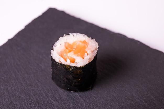 Il rotolo makisushi si trova sul piatto in ceramica nera Foto Gratuite