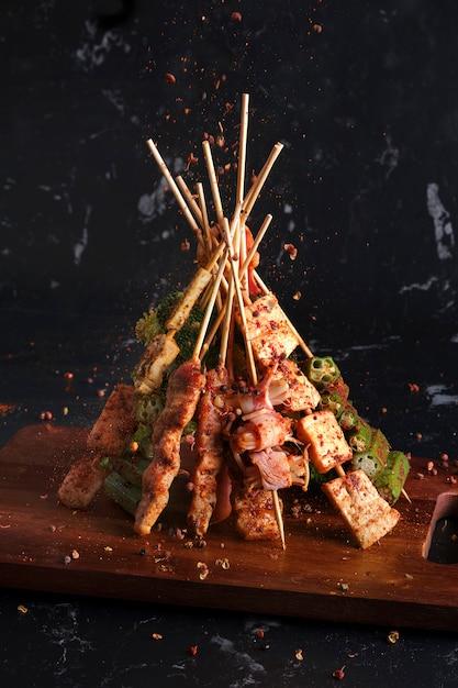 Малая гриль (барбекю) с сычуаньским перцем, падающими приправами, порошком мала и чили, горячей, острой и вкусной уличной едой. Premium Фотографии