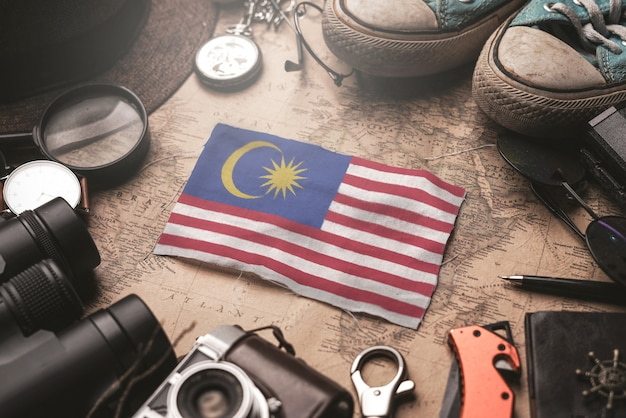Malaysia flag between traveler's accessories on old vintage map. tourist destination concept. Premium Photo