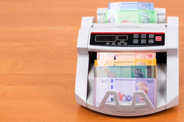 Malaysian money in a counting machine Premium Photo