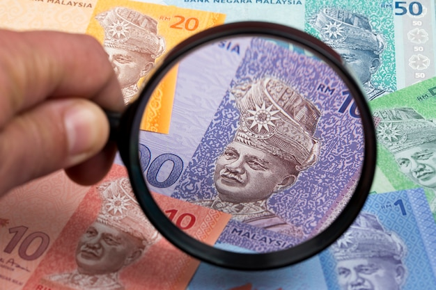 Malaysian money in a magnifying glass a business background Premium Photo