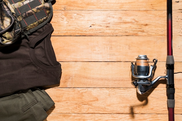 Male accessories and fishing rod on wooden desk Free Photo