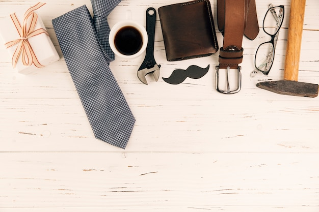 Male accessories near gift and cup of drink Free Photo