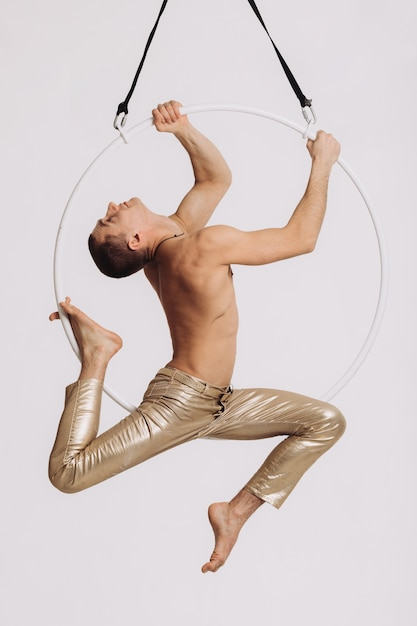 Male aerial gymnast performs acrobatic element in the ring Premium Photo