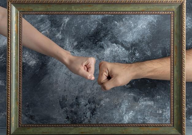 남성과 여성의 주먹이 액자 중간에서 만난다. 무료 사진