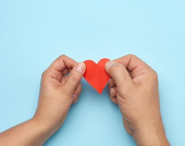 Мужская и женская рука держит красное бумажное сердце Premium Фотографии